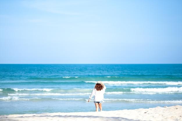 Eine frau, die am strand mit dem hintergrund des meeres und des blauen himmels spaziert