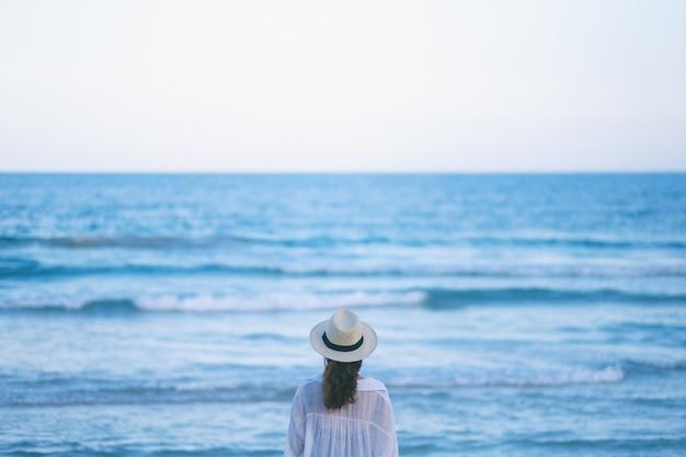 Eine frau, die am strand steht und ein schönes meer und blauen himmel allein betrachtet