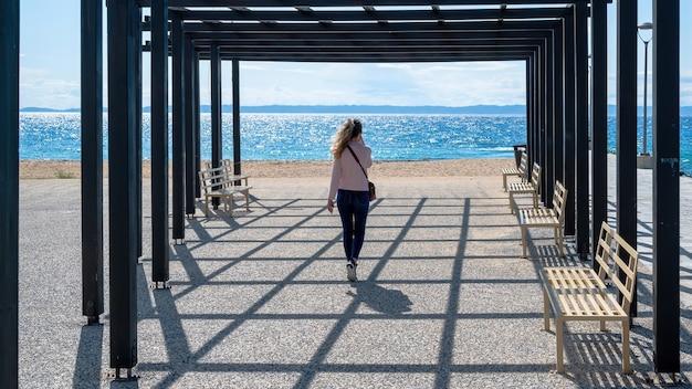 Eine frau, die am telefon in einem pavillon auf einem pier mit schwarzen metallpfosten und einer bänke, ägäisches meer in nikiti, griechenland spricht