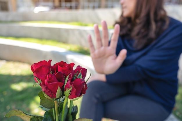 Eine frau, die am valentinstag eine rote rosenblume von jemandem ablehnt