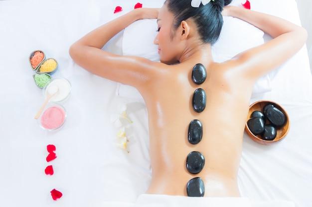 Eine frau, die an einem gesundheitsbadekurort beim haben einer heißen steinbehandlung oder -massage sich entspannt