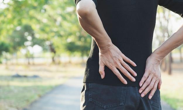 Eine frau, die an rückenschmerzen, rückenverletzung und muskelproblemen im freien leidet.