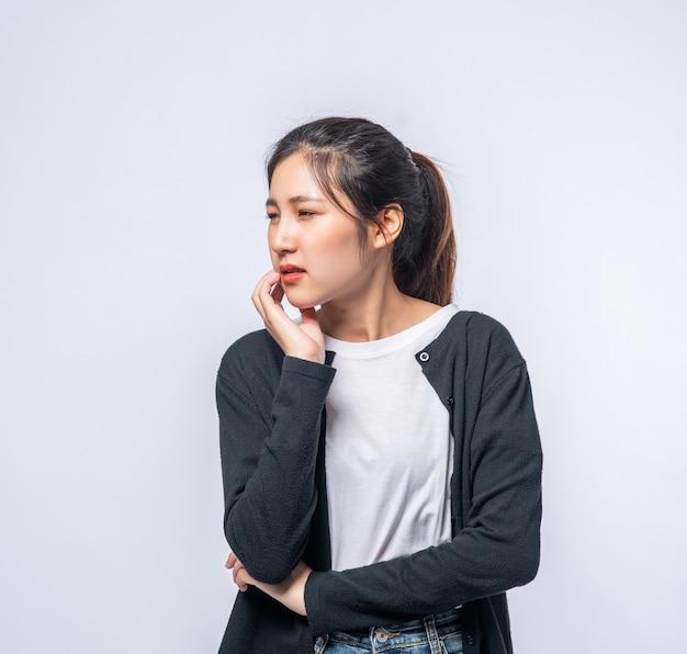 Eine frau, die an zahnschmerzen leidet und eine hand auf der wange hält