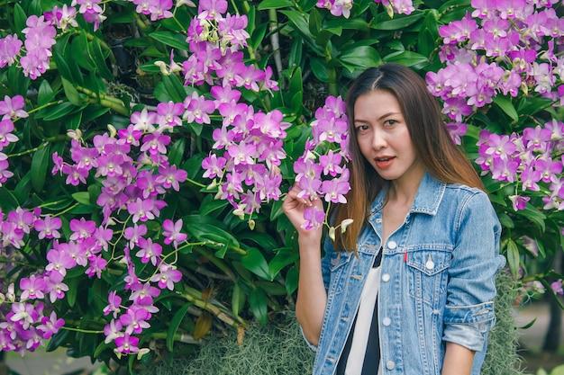 Eine frau, die auf einem schönen rosa orchideenblühen steht