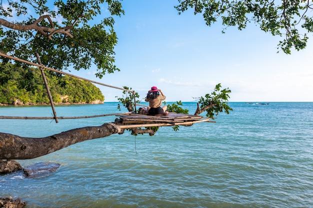 Eine frau, die auf einem zweig auf baum im meer am railay-strand, krabi, thailand sitzt
