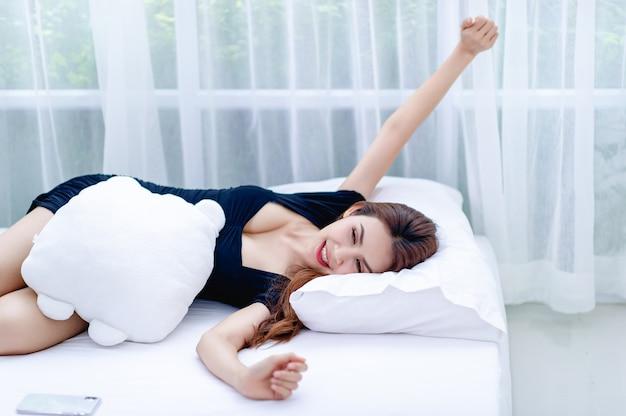 Eine frau, die auf einer weißen matratze schläft konzepte von schlaf und erholung für eine gute gesundheit