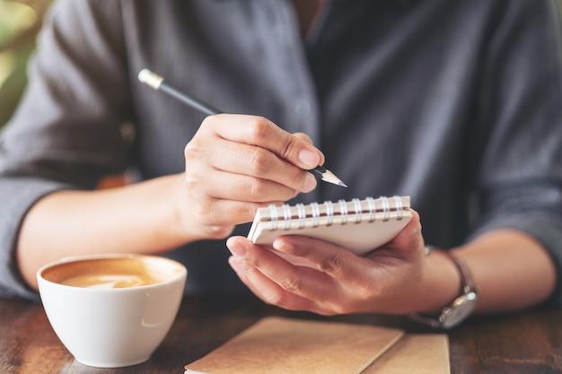 Eine frau, die auf leerem notizbuch mit kaffeetasse auf holztisch hält und schreibt