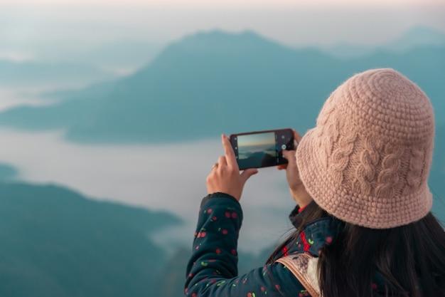 Eine frau, die bilder mit einem smartphone bergblick und morgensonne macht
