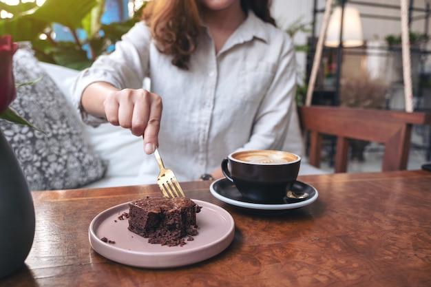 Eine frau, die brownie-kuchen mit gabel mit kaffeetasse auf holztisch im café schneidet