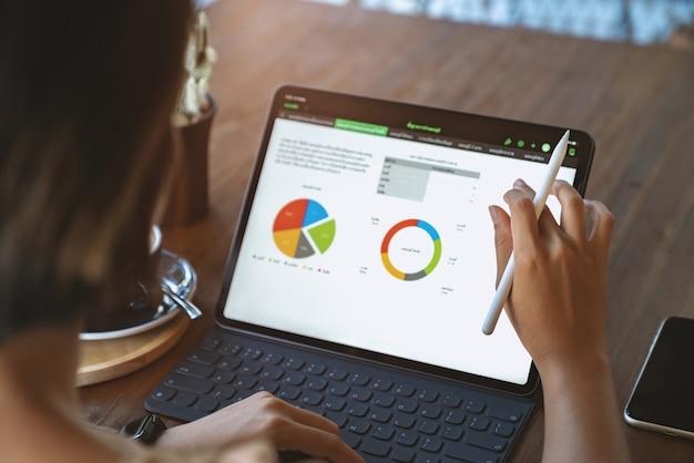 Eine frau, die die third-person-ansicht eines digitalen tablets verwendet