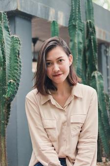 Eine frau, die ein braunes hemd sitzt mit einem kaktus trägt
