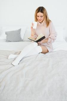 Eine frau, die ein buch liest und lächelt, als sie im bett sitzt. der wecker auf dem schreibtisch neben ihr.