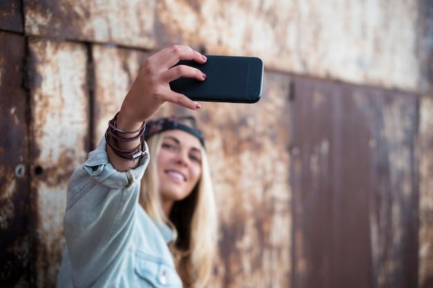 Eine frau, die ein foto von sich auf der straße macht - blonde teenager-dame, die ein selfie mit einem städtischen hintergrund macht - nahaufnahme des telefons
