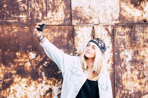 Eine frau, die ein foto von sich auf der straße macht - blonde teenager-dame, die ein selfie mit einem städtischen hintergrund macht