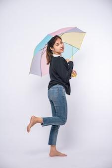 Eine frau, die ein schwarzes hemd trägt und mit einem regenschirm steht