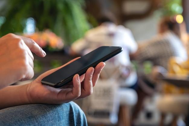 Eine frau, die ein schwarzes smartphone mit unscharfem hintergrund im café verwendet und darauf zeigt