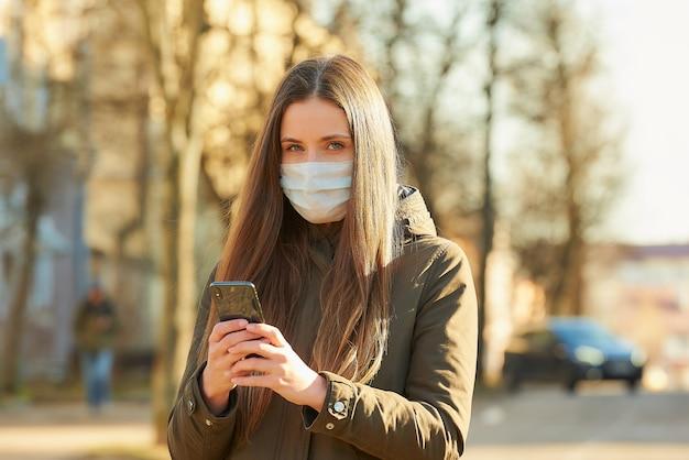 Eine frau, die ein smartphone benutzt, trägt eine medizinische gesichtsmaske, um die ausbreitung des coronavirus auf einer stadtstraße zu vermeiden