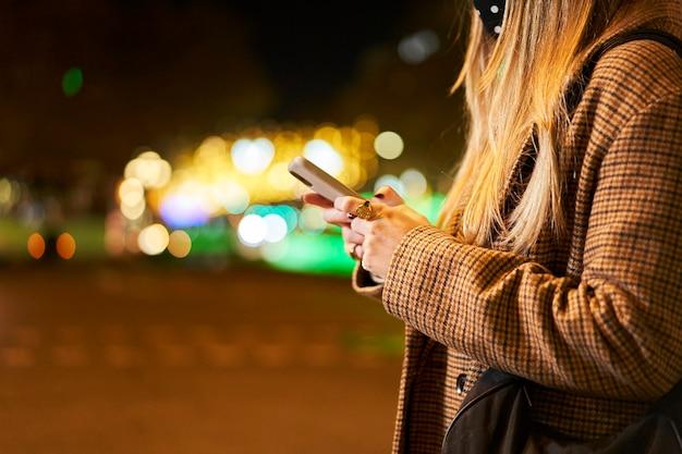 Eine frau, die ein smartphone draußen in einer stadt in der nacht hält.