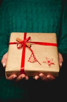 Eine frau, die ein weihnachtsgeschenk hält