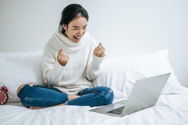 Eine frau, die ein weißes hemd auf dem bett trägt und glücklich laptop spielt.