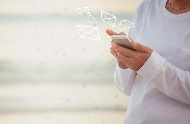 Eine frau, die eine e-mail mit einem smartphone sendet