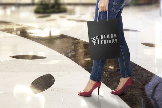 Eine frau, die eine einkaufstasche mit black friday-text trägt