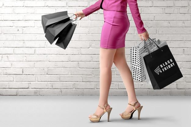 Eine frau, die eine einkaufstasche mit black friday-text über wand trägt