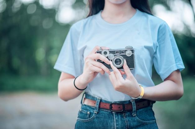 Eine frau, die eine kamera, eine frau hält, die fotografie liebt. nahaufnahme fotografie