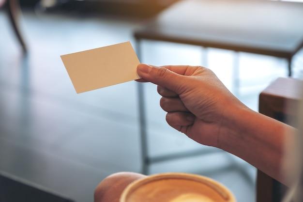 Eine frau, die eine leere visitenkarte hält, während kaffee trinkt