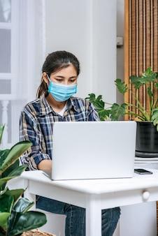 Eine frau, die eine maske trägt, benutzt einen laptop, um zu arbeiten.