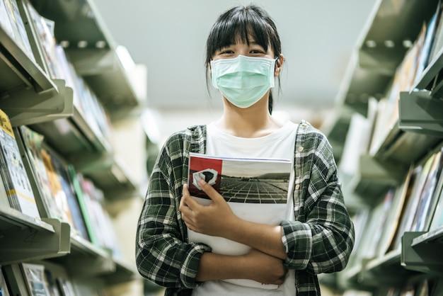 Eine frau, die eine maske trägt und in der bibliothek nach büchern sucht.