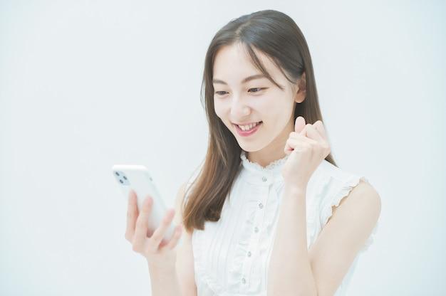 Eine frau, die eine mutpose macht, während sie auf den bildschirm eines smartphones schaut