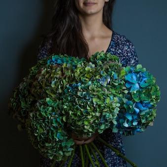Eine frau, die einen blumenstrauß des dekorativen grünen und blauen blattes hält, blüht in der hand auf raumwand