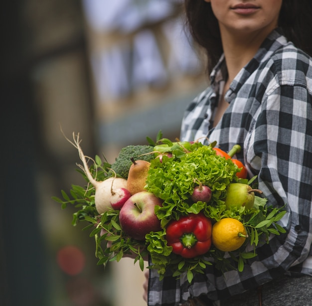 Eine frau, die einen blumenstrauß des gemüses und der früchte in der hand auf straße hält