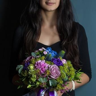 Eine frau, die einen blumenstrauß von saisonblumen in der hand hält