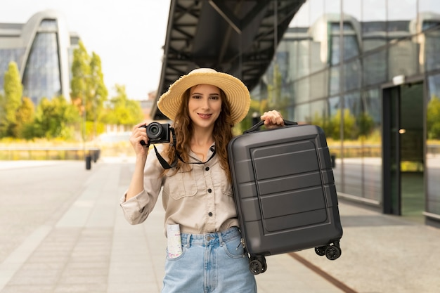 Eine frau, die einen koffer und eine kamera in ihren händen hält