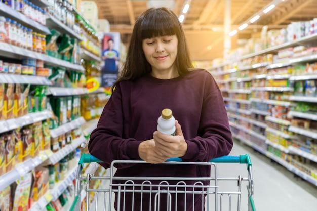 Eine frau, die einen produktaufkleber mit warenkörben am supermarkt liest. shopping-konzept
