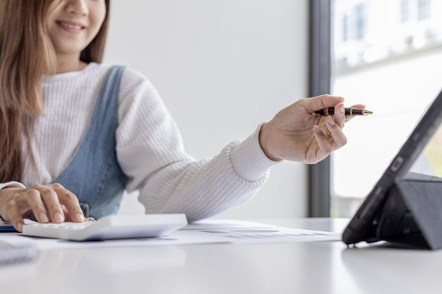 Eine frau, die einen stift hält, der auf einen tablet-bildschirm zeigt und einen taschenrechner drückt, überprüft die zahlen auf den finanzdokumenten, die die finanzabteilung vorbereitet hat. konzept der wirtschaftsprüfung
