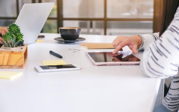 Eine frau, die einen tablet-pc mit handy und kaffeetasse auf dem tisch benutzt und mit dem finger auf sie zeigt