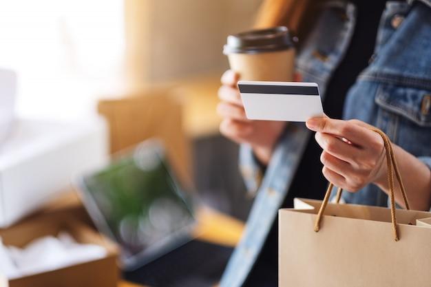 Eine frau, die einkaufstaschen, kreditkarte und kaffeetasse für online-einkaufskonzept hält