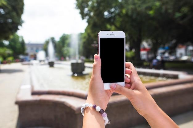 Eine frau, die foto des brunnens durch mobiltelefon im garten macht