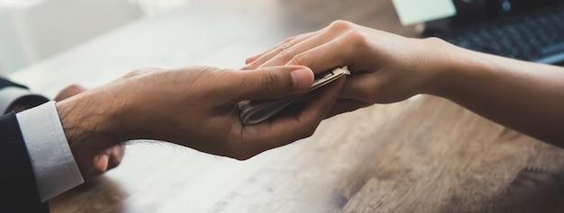 Eine frau, die geld in geschäftsmannhand einsetzt