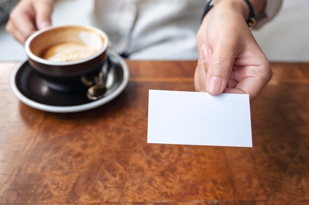 Eine frau, die hält und jemandem eine leere leere visitenkarte gibt, während sie kaffee trinkt