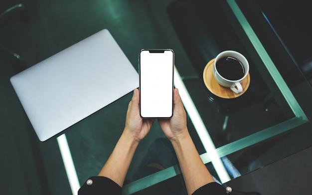 Eine frau, die handy mit leerem weißen desktop-bildschirm mit laptop und kaffeetasse auf dem tisch hält