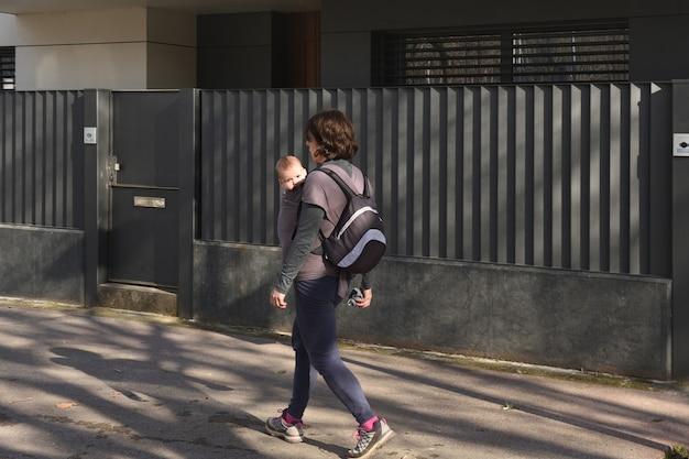 Eine frau, die ihr kind trägt, trainiert in einer städtischen umgebung