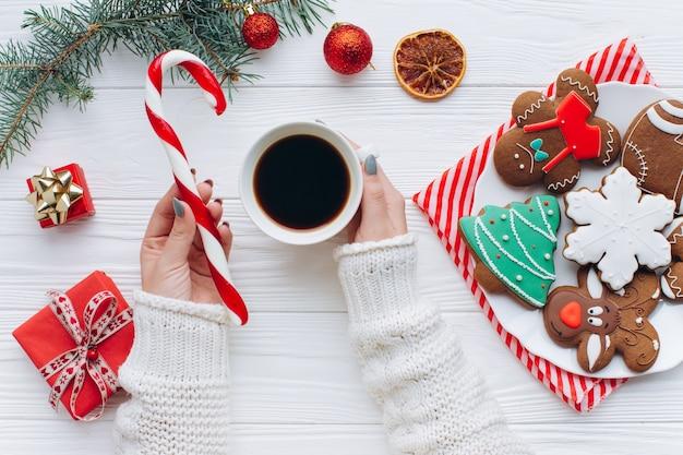 Eine frau, die in heißem kaffee der hände, zuckerstange mit weihnachtsdekorationen hält.