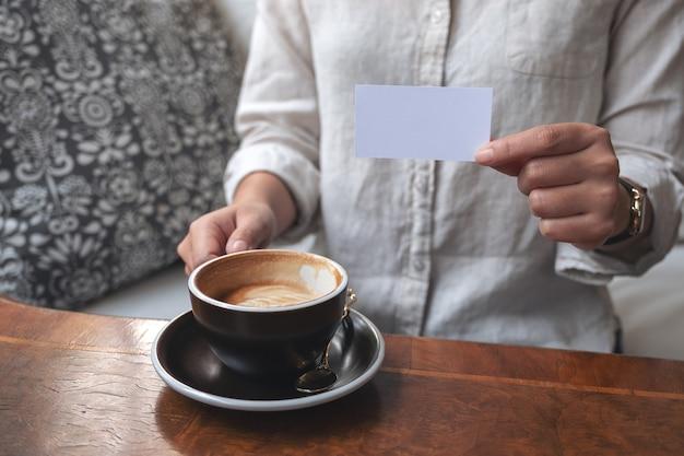 Eine frau, die jemandem beim kaffeetrinken eine leere visitenkarte hält und zeigt
