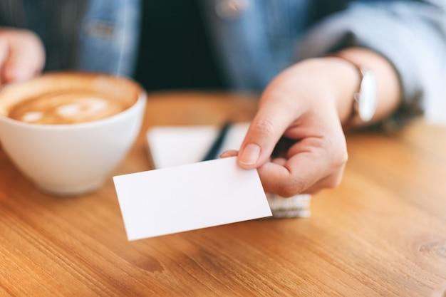 Eine frau, die jemandem eine leere leere visitenkarte hält und gibt, während sie kaffee trinkt