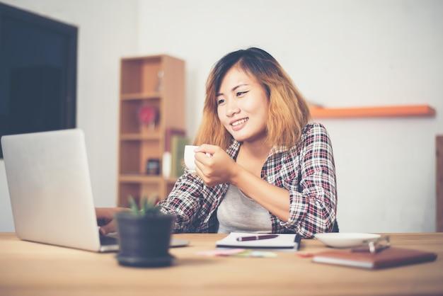 Eine frau, die kaffee durch den computer zu trinken