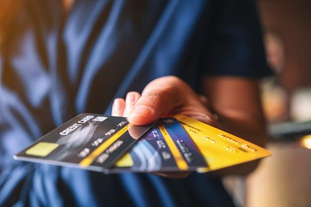 Eine frau, die kreditkarten hält und zeigt